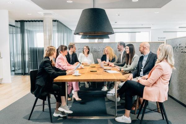 Personen unterhalten sich an großen Tisch - Team minds&maker