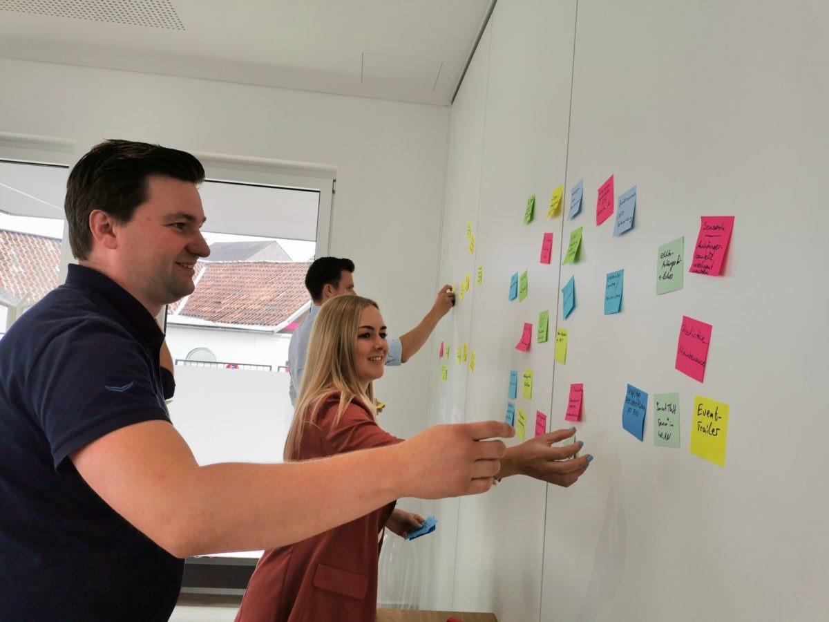 Workshop Teilnehmer kleben Post-Its an die Wand